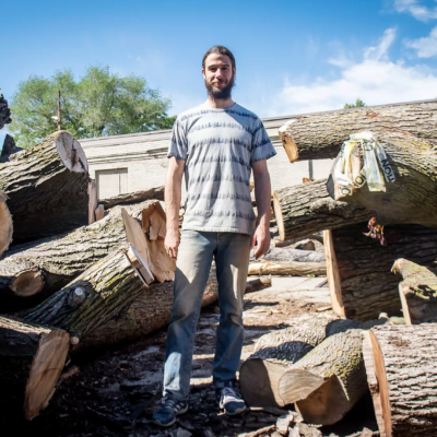 Man standing amongst large logs